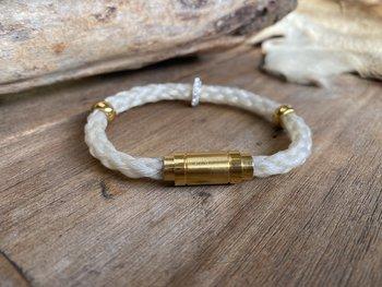 Rondgevlochten armband met goudkleurige sluiting.